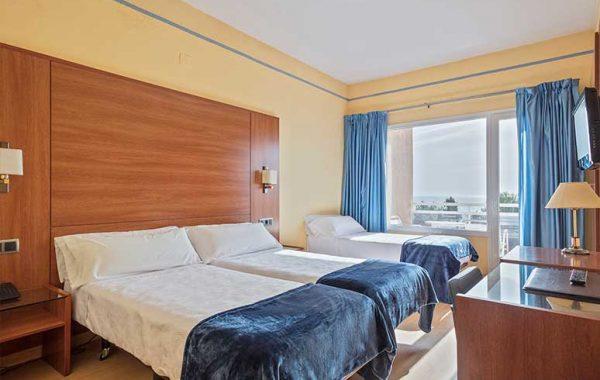 Habitación Triple con tres camas, baño con bañera y balcón con vistas al mar